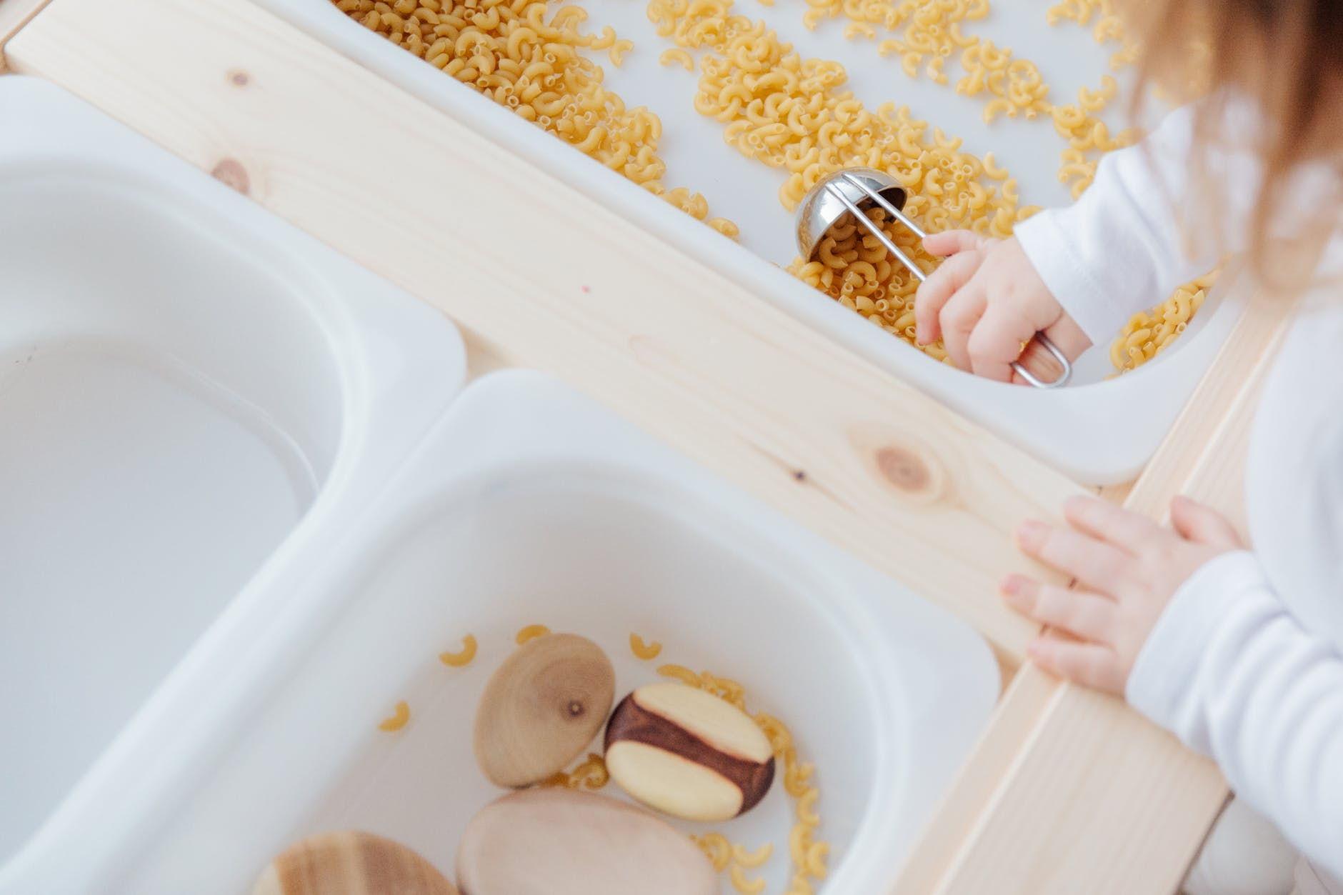 little girl collect raw pasta with metal spoon in plastic container